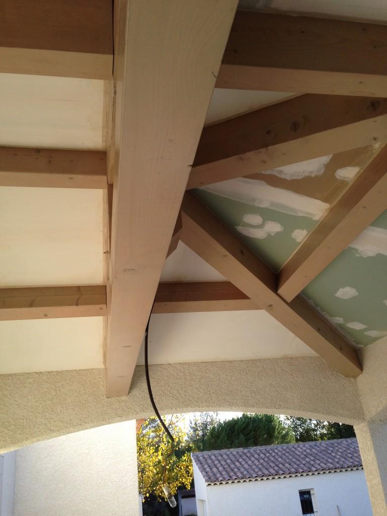 Réalisation d'un faux plafond sous le toit d'une terrasse.<br /> <br /> Les plus gros éléments de la charpente sont conservés et mis en valeur à l'aide d'une lasure grise satinée.<br /> Les faux-plafonds sont réalisés à l'aide de Placo-plâtre puis peints en blanc mat.