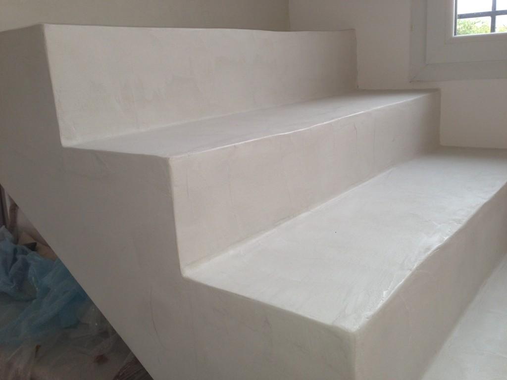 Réalisation d'un béton ciré taloché sur escalier brut en ciment.<br /> <br /> Application d'une résine d'accrochage suite au masquage rigoureux des murs.<br /> Création de la couleurs à base de pigments très clair ( Nacre/Ivoire )<br /> Première couche de béton ainsi qu'un séchage complet du produit.<br /> Deuxième couche de béton en papillonnage et en fine couches, suite à ce processus les marches sont ferrées.<br /> <br /> Application d'un bouche pores en plusieurs passes successives.<br />